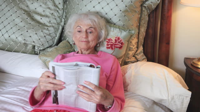 ms senior woman reading magazine in bed / portland, oregon, usa - portland oregon点の映像素材/bロール