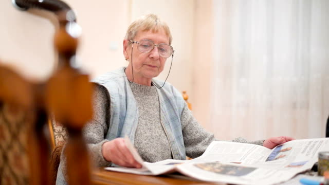 senior woman reading newspaper - newspaper page stock videos and b-roll footage