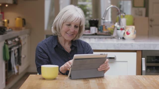 Senior woman reading on digital tablet on kitchen table