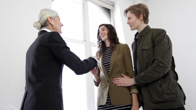 MS Senior woman real estate agent handing over apartment keys to young couple / New York City, New York, USA