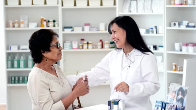 senior woman receives prescription from female pharmacist - mid adult women stock videos & royalty-free footage