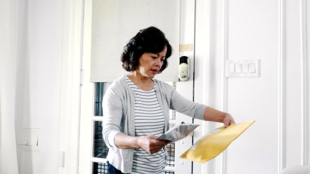 senior woman receives two packages - letter document stock videos & royalty-free footage