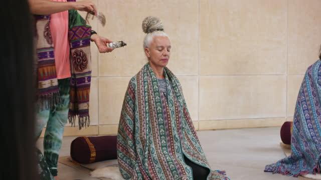 Senior woman receiving smudge stick smoke therapy in yoga studio