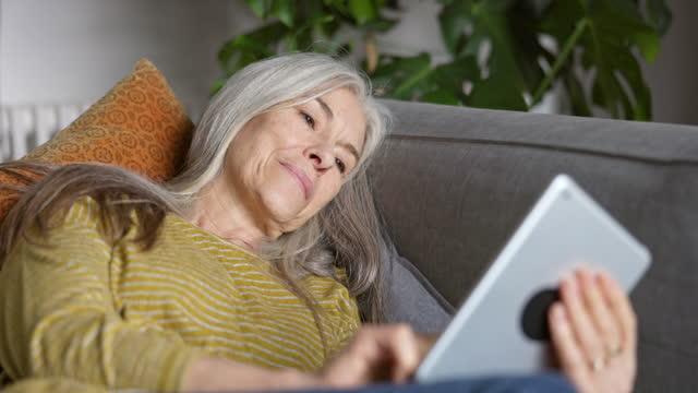 vídeos de stock e filmes b-roll de senior woman reclining on sofa using digital tablet - vida real
