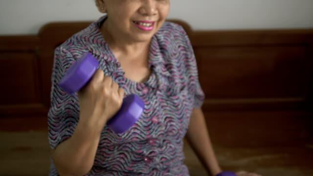 stockvideo's en b-roll-footage met senior vrouw ontspanning oefening thuis - 65 69 jaar