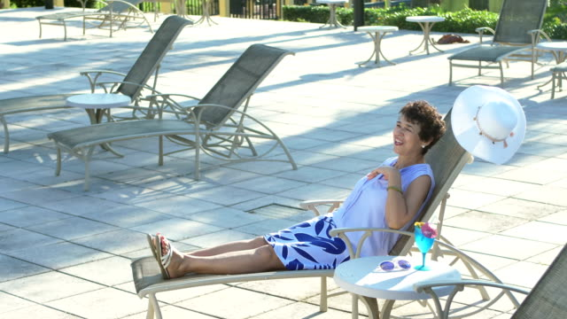 senior woman relaxing on lounge chair, tropical drink - tropical drink stock videos & royalty-free footage