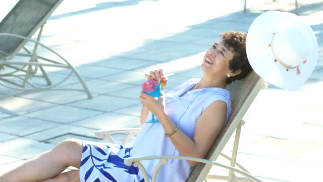 Senior woman relaxing on lounge chair, tropical drink