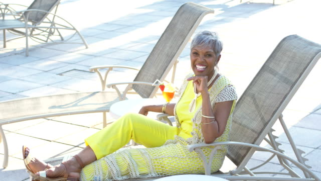 senior woman relaxing on lounge chair - tropical drink stock videos & royalty-free footage