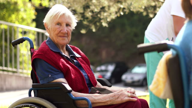senior woman relaxing outdoors in retirement community - wheelchair stock videos and b-roll footage