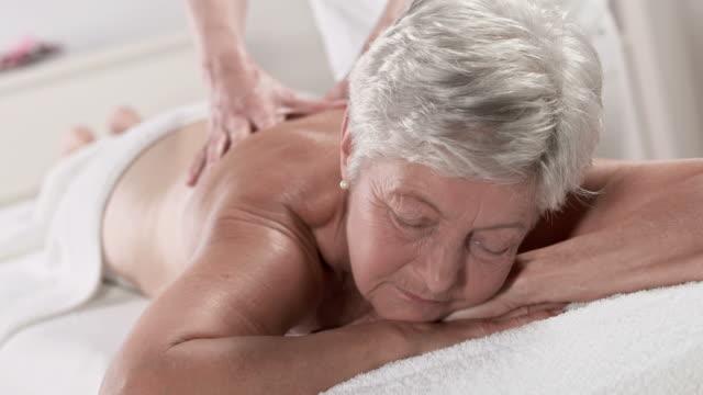 HD: Senior mulher relaxante durante a Massagem nas costas