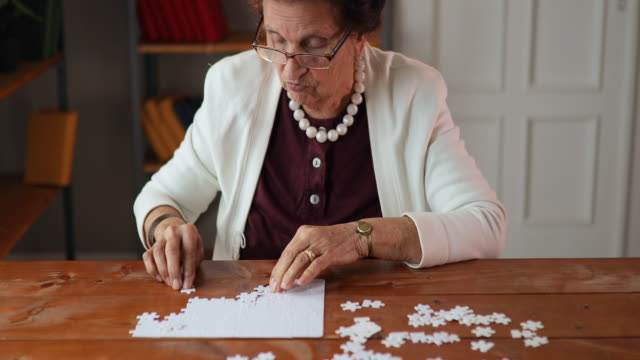senior woman relaxing with jigsaw puzzle at home - puzzle stock videos & royalty-free footage