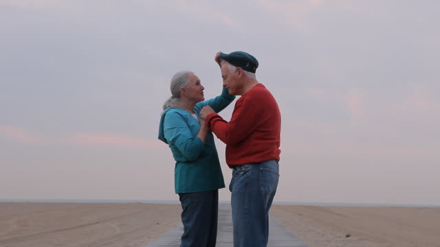 ms senior woman removes senior mans cap and gives him kiss on beach boardwalk / los angeles, california, usa - falling in love stock videos and b-roll footage