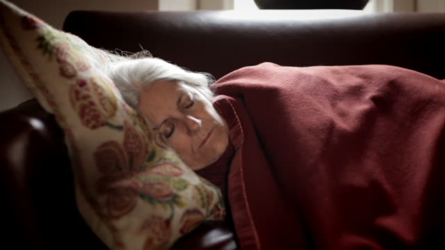 |ms senior woman resting on couch / kingston, new york, usa  - bed sheets stock videos & royalty-free footage