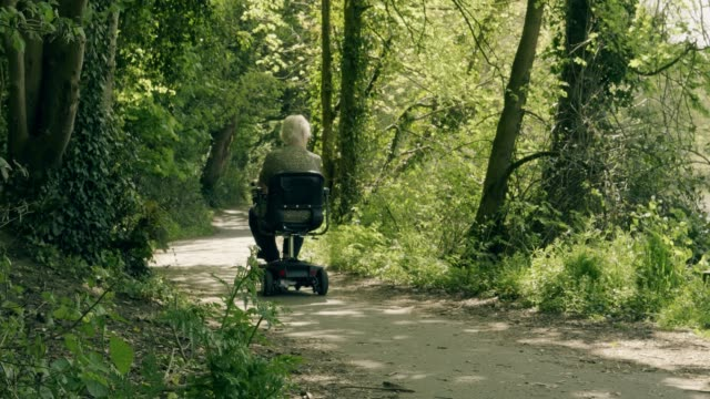 senior woman riding a mobility scooter. rear view. - kent england stock videos & royalty-free footage