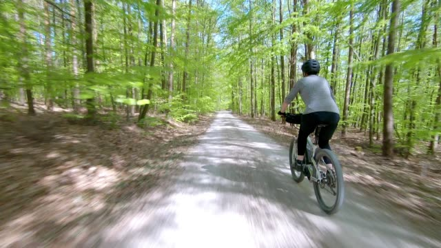 senior woman riding electric mountain bike in spring forest - bicycle trail outdoor sports stock videos & royalty-free footage