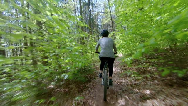 春の森で電動マウンテンバイクに乗るシニア女性 - クロスカントリーサイクリング点の映像素材/bロール