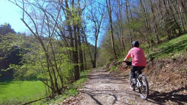 vídeos de stock, filmes e b-roll de bicicleta de montanha elétrica da equitação da mulher sênior no dia ensolarado - ponto de vista de câmera
