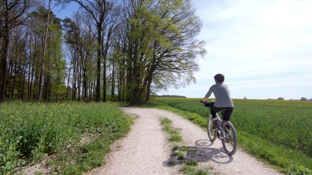senior woman riding electric mountain bike - cycling stock-videos und b-roll-filmmaterial