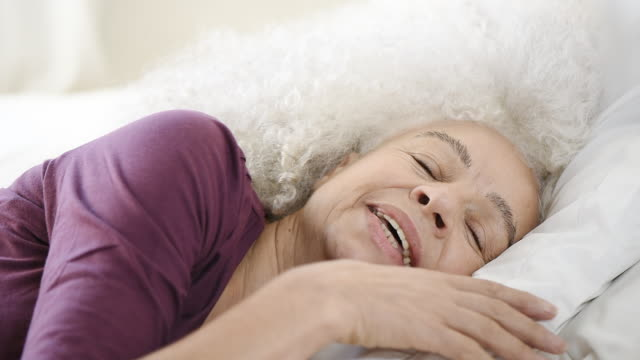senior woman rolling over in bed