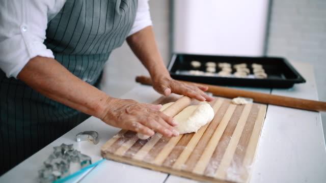 vídeos de stock, filmes e b-roll de massa da pastelaria do rolamento da mulher sênior em sua home - comida doce