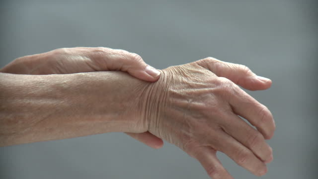 CU Senior woman rubbing wrist and thumb, New York City, New York, USA