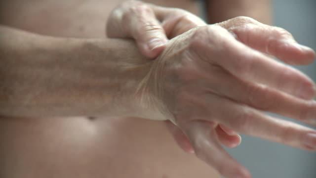 ECU Senior woman rubbing wrist, New York City, New York, USA