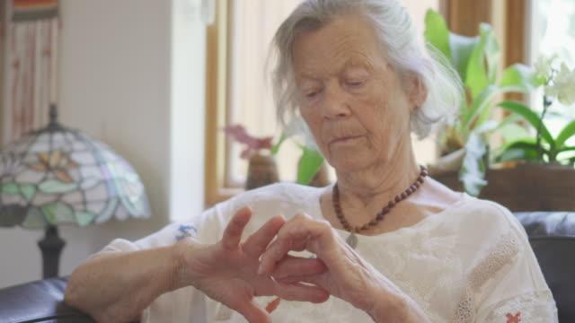 vídeos y material grabado en eventos de stock de mujer mayor se frota las manos - herida