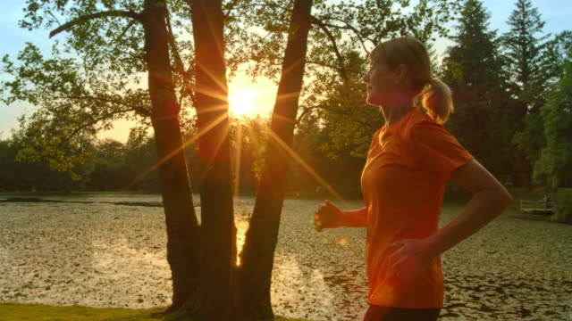 SLO MO TS Senior woman running along lake at sunset