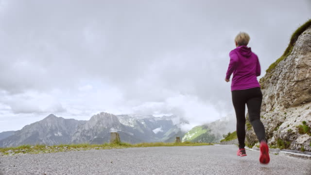 ds senior woman running down a road high in the mountains on a cloudy day - wide shot stock videos & royalty-free footage