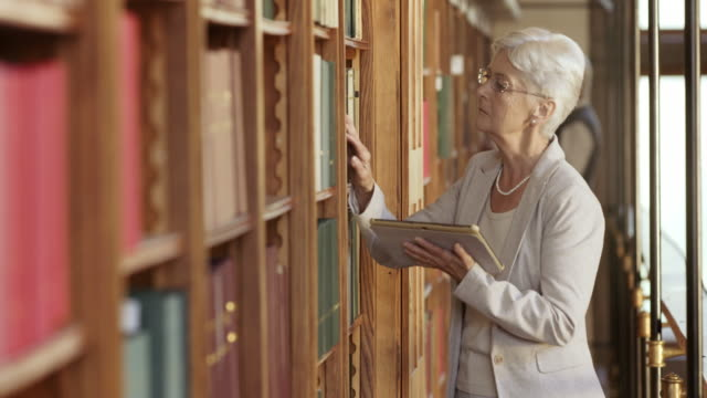 DS Senior woman searching for a book with a tablet in the library