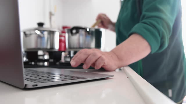 senior woman searching for new recipes with laptop on kitchen counter - eternity stock videos & royalty-free footage
