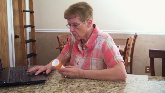 senior woman searching medicine - prescription medicine bottles stock videos & royalty-free footage