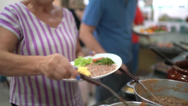 vídeos de stock, filmes e b-roll de mulher idosa selecionando alimentos no autoatendimento - buffet refeições