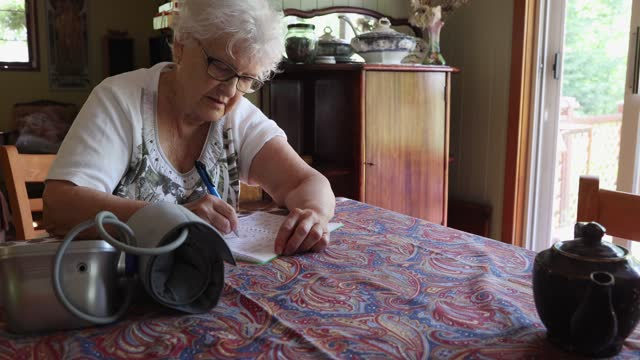 stockvideo's en b-roll-footage met senior woman self folding her blood pressure monitoring equipment and writing down results in her diary - alleen één oudere vrouw