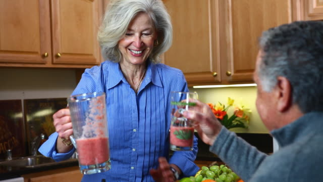 ms senior woman serving juice to man in kitchen / manchester, vermont, usa - detox stock videos & royalty-free footage