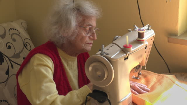 senior woman sewing a face mask to protect herself from corona virus - senior women stock videos & royalty-free footage