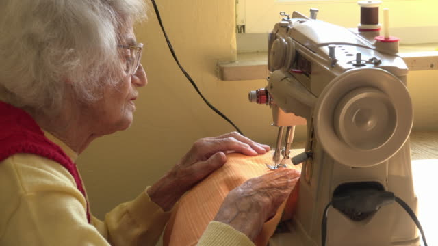 senior woman sewing a face mask to protect herself from corona virus - sewing machine stock videos & royalty-free footage
