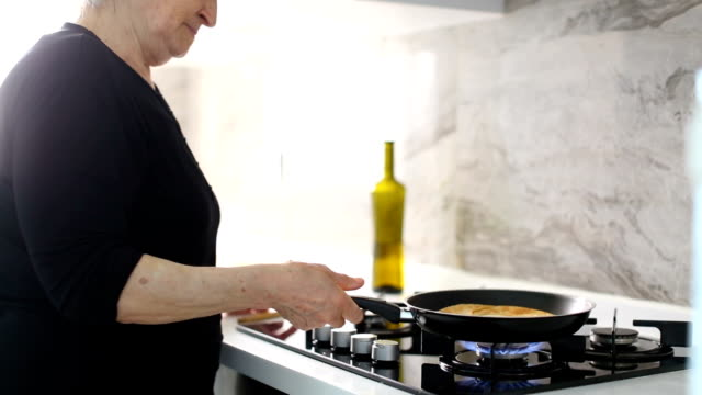 senior woman shaking the frying pan while cooking delicious flatbread in the kitchen - cucina mediterranea video stock e b–roll