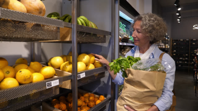 senior woman shopping at an organic food market looking at the prices of the food on the shelves and choosing the fruits - paper bag stock videos & royalty-free footage