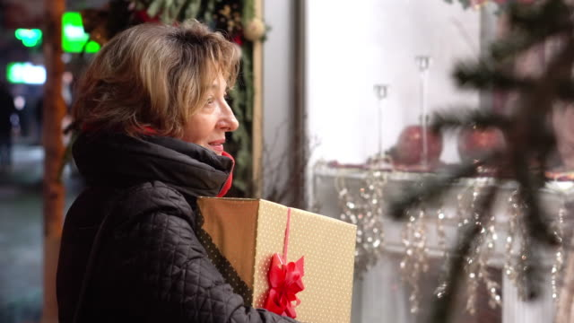 senior woman shopping for christmas at night - 60 64 years stock videos & royalty-free footage