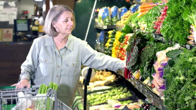 生産部門で食料品の買い物をするシニア女性 - チャード点の映像素材/bロール