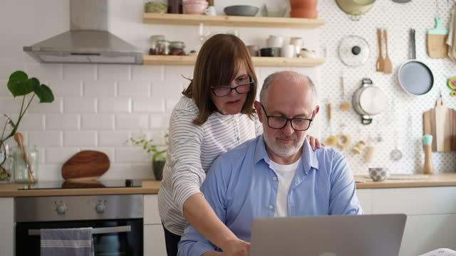 senior woman showing her husband how to use online banking - e mail stock videos & royalty-free footage