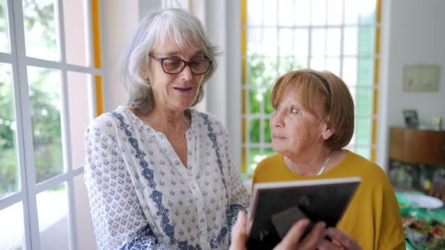 vídeos y material grabado en eventos de stock de mujer mayor mostrando la foto de sus nietos en un asilo de ancianos - marco