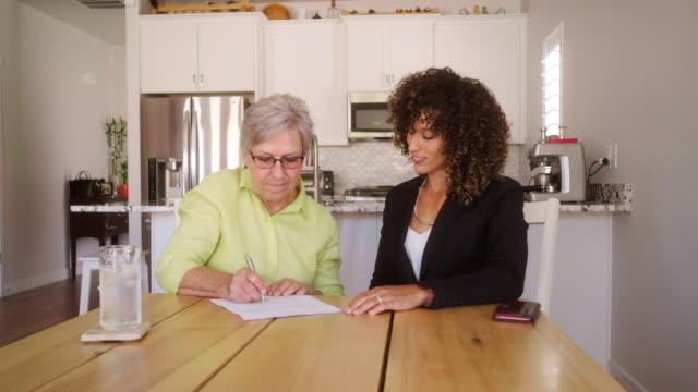 vídeos de stock, filmes e b-roll de originais de assinatura da mulher sênior em sua home - testamento