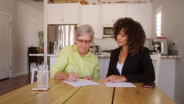 senior woman signing documents in her home - human age stock videos & royalty-free footage