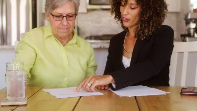 donna anziana firma documenti nella sua casa - strategia di vendita video stock e b–roll