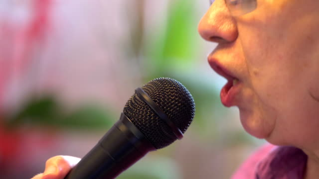 Senior woman signing karaoke with microphone in slow motion 4k