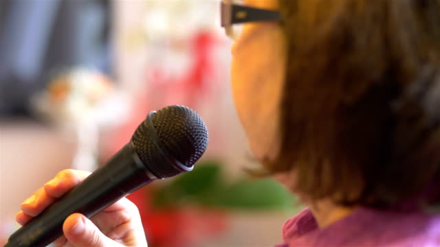 Senior woman signing with microphone karaoke in slow motion 4k