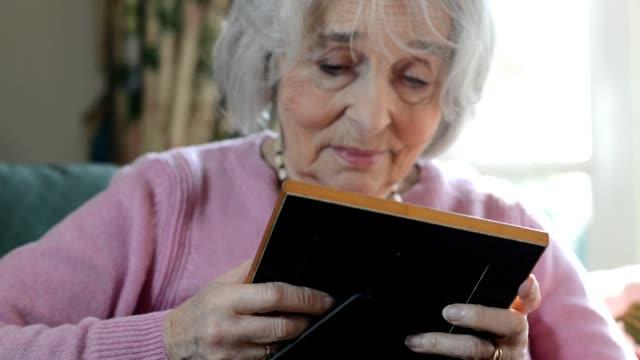Senior kvinna sitter i fåtölj hemma och ser på foto i ram medan leende nostalgiskt
