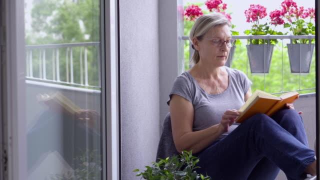 vidéos et rushes de femme aîné s'asseyant obalcony pendant l'isolement - femmes d'âge mûr